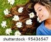 Woman lying in a floral garden with daisies around her head - stock photo