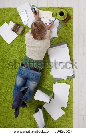 Woman lying on living room floor, doing financial calculation,holding credit card and pen, drinking coffee, in overhead view.