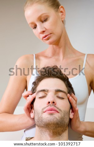 woman massaging man's temples