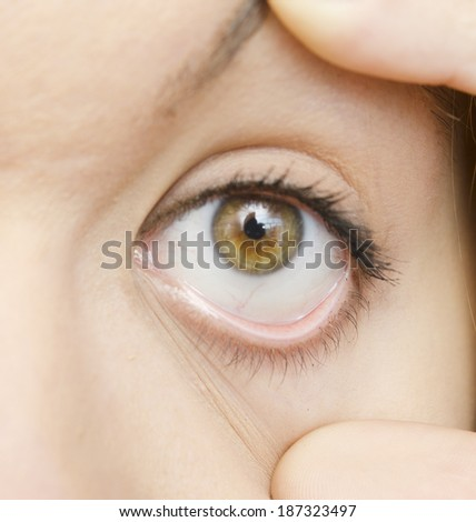 woman opened eye with fingers