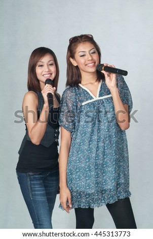 Woman or asian woman singing karaoke together