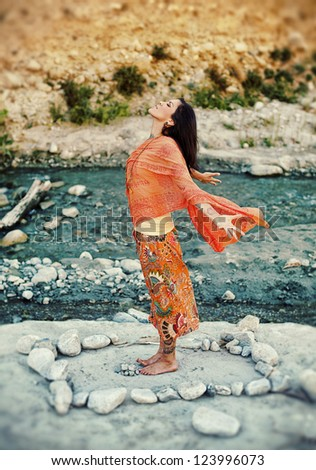 Woman outdoors near a river with her arms and heart open in a mandala of stones.