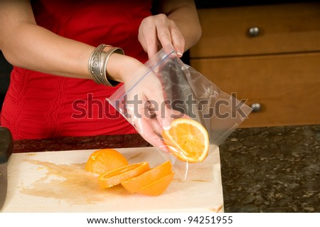 woman packages slices of orange