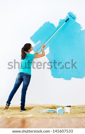 woman painting wall in new home