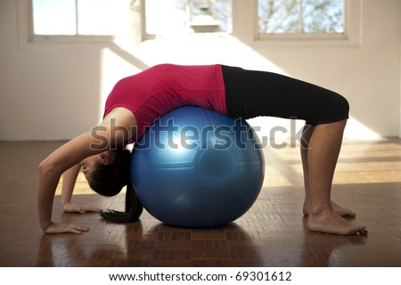 Woman performing yoga on a fitness-ball