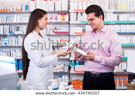 Woman pharmacist counseling customer about drugs usage in modern farmacy