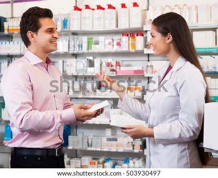Woman pharmacist  in a white coat offers the visitor a cure at the chemists shop