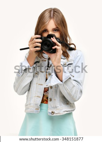 Woman photographer with digital camera, taking a picture while looking at the camera.