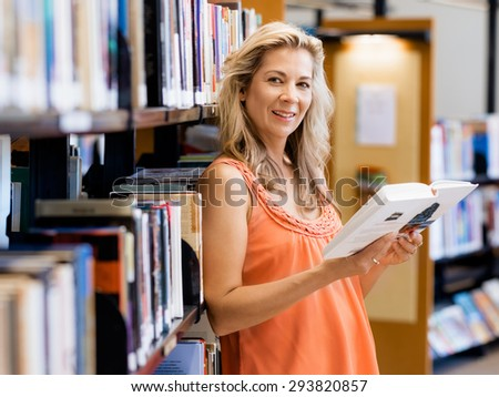 Woman picking a book in public library