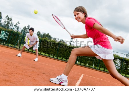 Woman playing doubles in tennis at a clay court