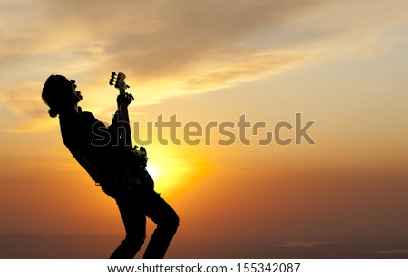 Woman playing guitar against the background of sunset