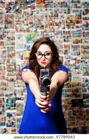 Woman pointing a vintage camera on a comic theme background