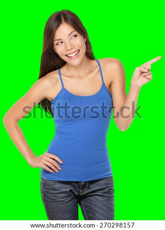Woman pointing happy showing and looking to the side - Isolated on green screen chroma key background. Beautiful young multiracial Caucasian / Chinese Asian female model in studio.