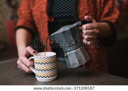 Woman pouring coffee from vintage coffee maker