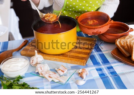 Woman pouring  Traditional Russian  soup with meat, beetroot and cabbage