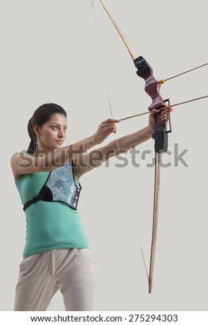 Woman practicing archery isolated over gray background