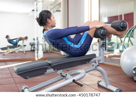 Woman practicing sit-ups on exercise machines at the gym and reflected at mirror on wall. Girl strengthens the muscles of the abdomen and back at the modern public gym club.