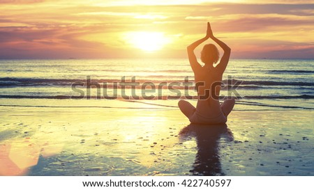 Woman practicing yoga at seashore during sunset.
