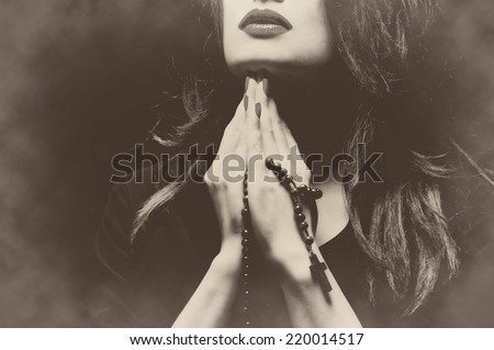 Woman praying with rosary sepia retro vintage