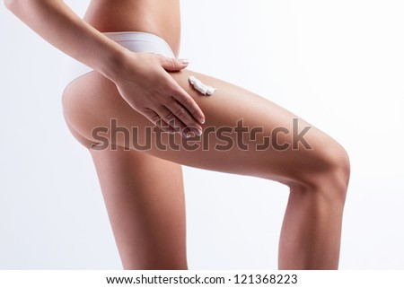 Woman put the cream on hips isolated