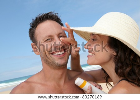 Woman putting sunblock on her boyfriend's nose