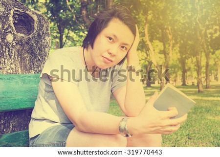 woman reading book in the park. book is in right hand - vintage effect