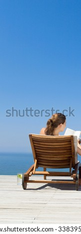 Woman relaxing in chair at the poolside