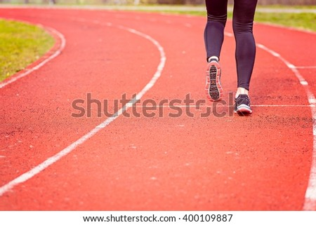 Woman run training outdoors. Young lady doing exercises and ready to start running. Health and sport concept.