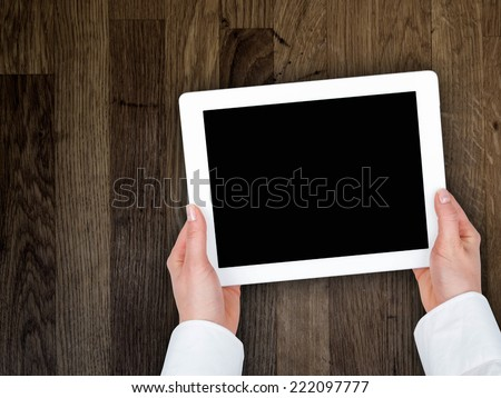 woman's hand holding a tablet on the background of a wooden tabletop