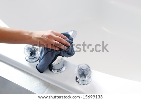 Woman's hand with microfiber cloth cleaning chrome tap