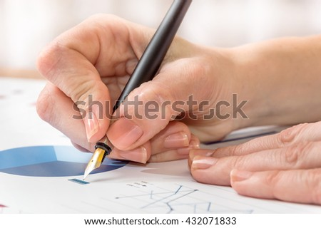 woman's hand with pen on the graphs