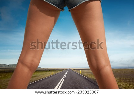 Woman's legs in the middle of an empty road in country side