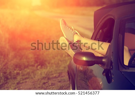 Woman's legs out of car windows in summer sunset