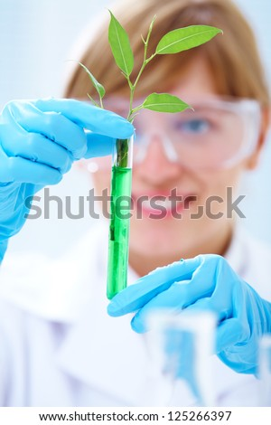Woman scientist holding a test tube with plant