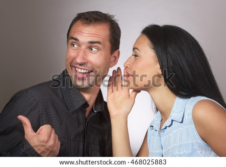 Woman sharing secret with surprised man