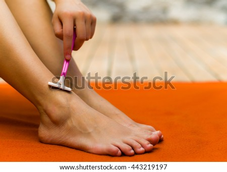 Woman shaving her legs with the left hand, her feet are on an orange background