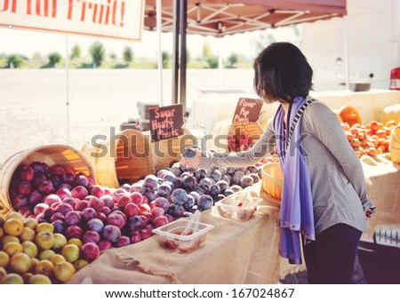 Woman shopping for fruit at an outdoor market