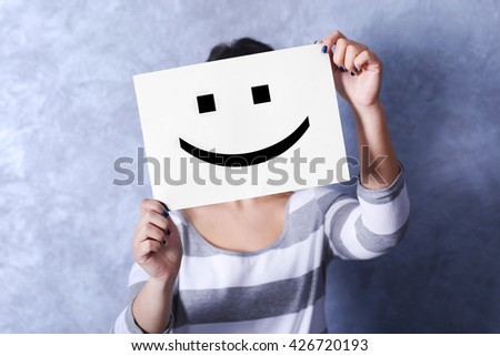 Woman showing a happy emoticon in front of face against a grey textured wall background
