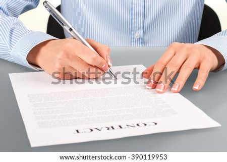 Woman signs contract at desk. Female signing contract at desk. Employer at the working desk. Recruiter at her workplace.