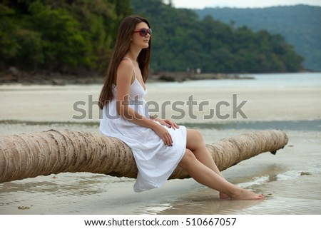 woman sit on log in beach