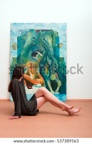 Woman sitting a gallery in front of oil on canvas