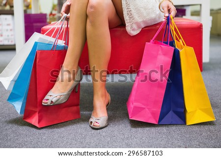 Woman sitting and holding shopping bags at a shoe shop