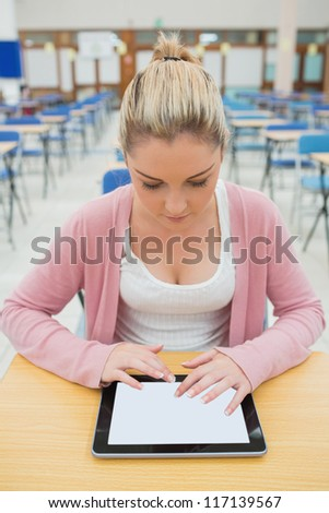 Woman sitting at desk in empty exam hall using tablet pc