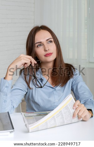 Woman sitting at table in office holding in one hand a newspaper, and in the other glasses and looking up