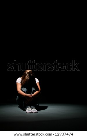 Woman sitting in a spotlight with her head on her knees.
