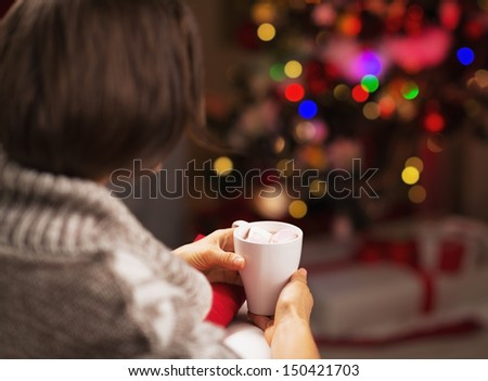Woman sitting in armchair with cup of hot chocolate in front of christmas tree . rear view