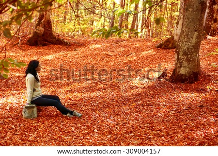 Woman sitting on the bench in autumn forest with trees and orange leaves