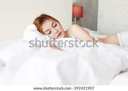 Woman sleeping on a white bed.