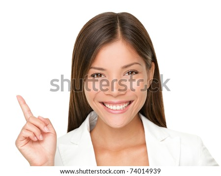 Woman smiling pointing up showing copy space. Closeup of beautiful young professional businesswoman isolated on white background.