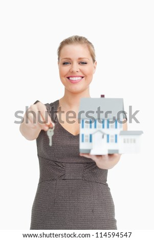 Woman smiling showing a model house and a key against white background